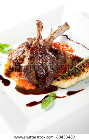 Roasted Lamb Chops on Tomato Sauce Garnished with Vegetables and Basil - stock photo