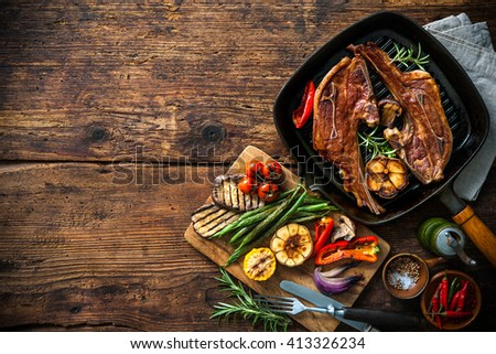 Roasted lamb meat with vegetables on grill pan on wooden background - stock photo