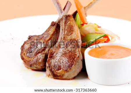 Roasted lamb ribs with fresh vegetables and sauce in a white bowl on a white plate.