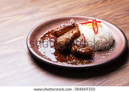 roasted lamb ribs with rice garnish - stock photo
