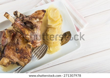 Roasted leg lamb with potatoes on the table of the kitchen - stock photo