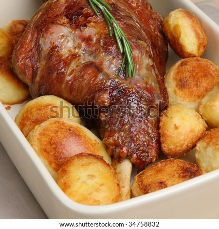 Roasted leg of lamb with roast potatoes - stock photo
