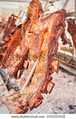 Roasted meat of beef cooked on a vertical grills placed around fire. Asado, traditional barbecue dish in Argentina