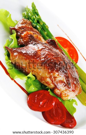 roasted meat served with asparagus on ceramic plate - stock photo