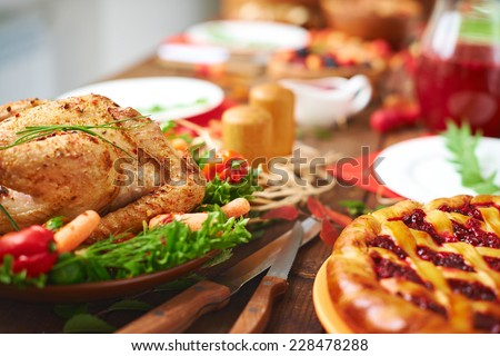Roasted meat with garnish and cowberry pie on festive table - stock photo