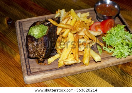 roasted meat with sauce and fried potatoes on a wooden table - stock photo