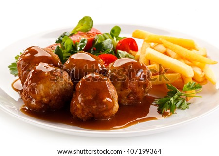Roasted meatballs, chips and vegetables  - stock photo