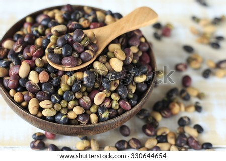 roasted mixed nut. roasted mixed pea. mixed nut. roasted mixed nut in wooden cup or wooden spoon on wooden white background. healthy food. healthy snack. cooked nuts