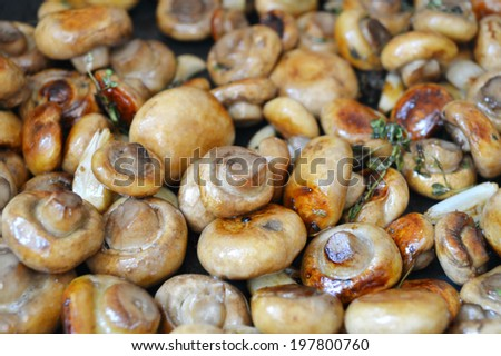 Roasted mushrooms champignons with thyme and garlic in a pan - stock photo