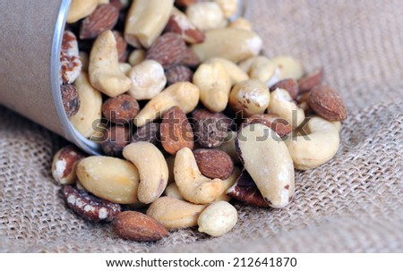 roasted nuts fall out from can (shallow deep of field) - stock photo