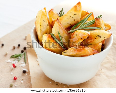 Roasted or baked potatoes with rosemary in a white bowl on wooden background - close up rustic composition - stock photo