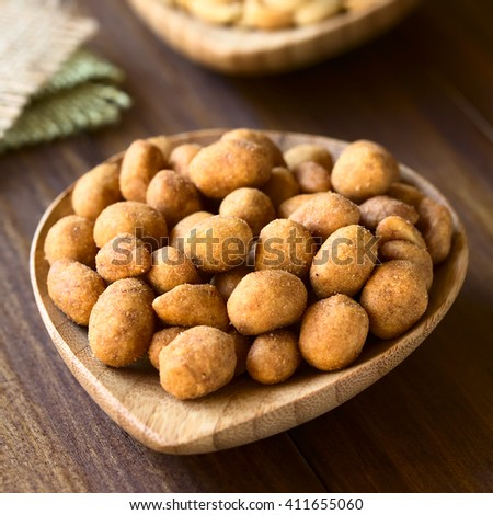 Roasted peanuts in spicy coat, photographed on dark wood with natural light (Selective Focus, Focus one third into the peanuts)