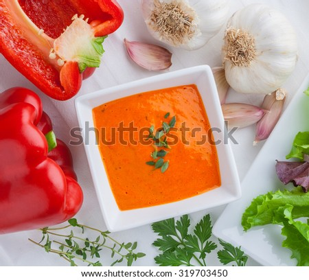 Roasted pepper dip sauce, spread in  bowl with garlic, lettuce, parsley, oregano. - stock photo