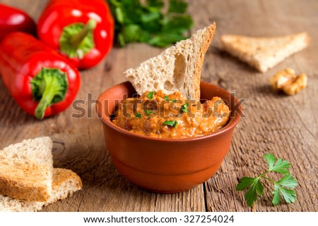 roasted pepper dip with nuts and bread in ceramic bowl over rustic wooden background closeup - stock photo