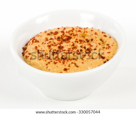 Roasted Pepper Hummus in a white bowl.