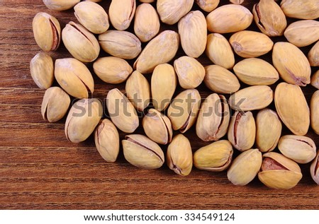 Roasted pistachio nuts on natural wooden table background, healthy food and nutrition