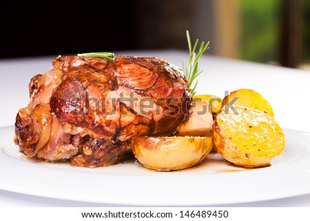 Roasted pork knuckle with potatoes - stock photo