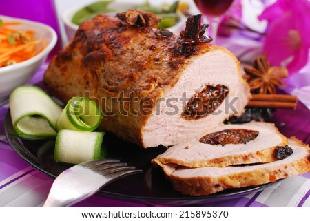 roasted pork loin stuffed with prune and spices on festive table - stock photo