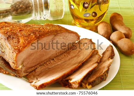 roasted pork on a white plate among spices