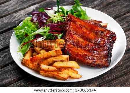 Roasted Pork Rib,  Fried Potato on white plate with Vegetables. - stock photo