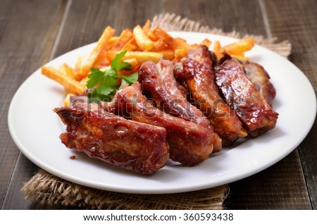 Roasted pork ribs and potato fries on white plate, close up view - stock photo
