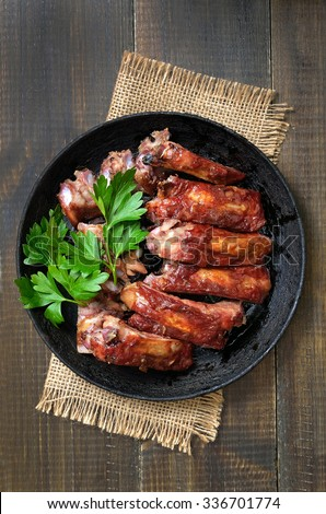 Roasted pork ribs in frying pan, top view - stock photo