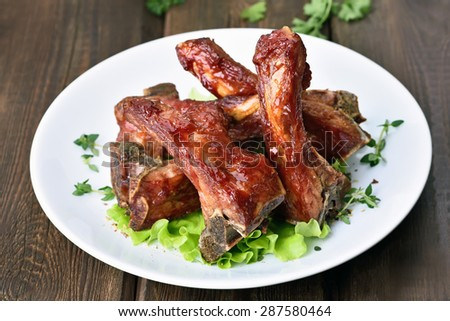 Roasted pork ribs on white plate over wooden table - stock photo