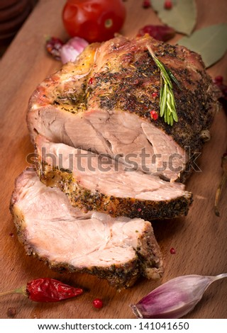 Roasted pork with spices on wooden board - stock photo