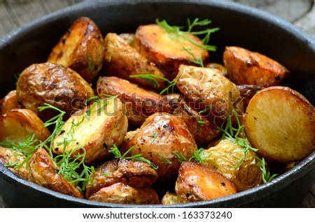 Roasted potato in a frying pan, close up view