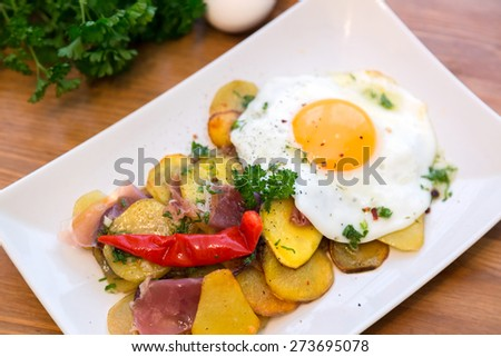 Roasted potato topped with chili and egg - stock photo