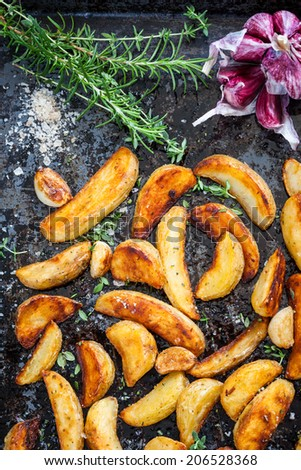 Roasted potato wedges with herbs and garlic on a baking tray - stock photo