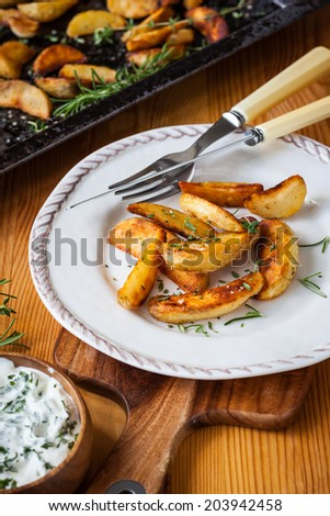 Roasted potato wedges with herbs and garlic on a plate