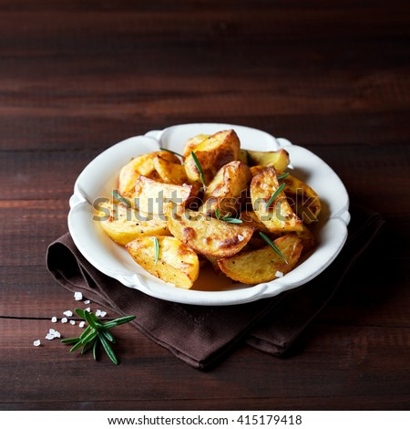Roasted potato wedges with rosemary on plate, selective focus - stock photo