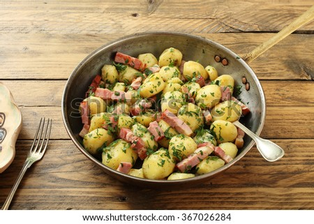 roasted potato with bacon in metal pan on rustic background