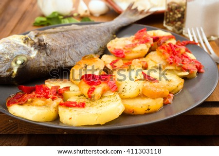 roasted potatoes and  sea bream on wooden classic