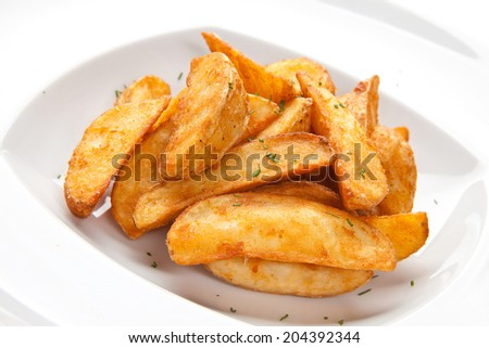 Roasted potatoes on a white plate on a white background isolated closeup - stock photo