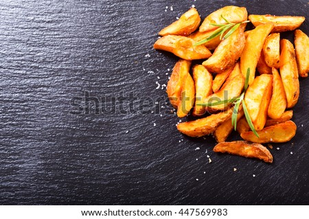 roasted potatoes with rosemary on dark background