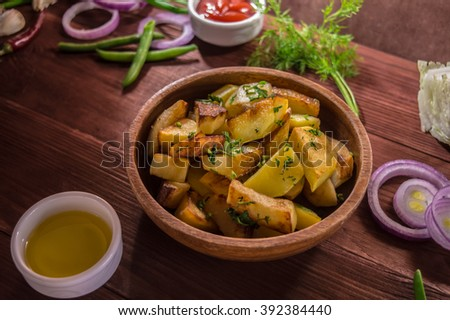 Roasted potatoes with vegetables and herbs on a wooden background  - stock photo