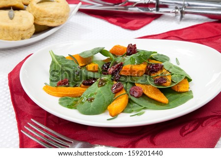 Roasted pumpkin and spinach salad, sage biscuits, and carved roasted spiced ham appetizers with Christmas ornaments.  - stock photo