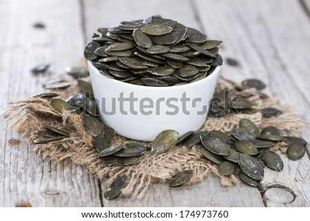 Roasted Pumpkin Seeds (macro shot) on vintage wooden background - stock photo