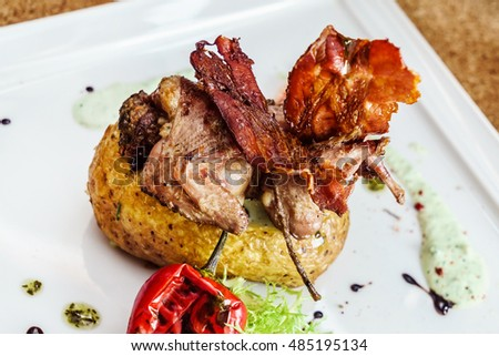 Roasted quail on a bed with roasted potatoes