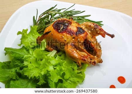 Roasted Quail with rosemary and spices on the wood background