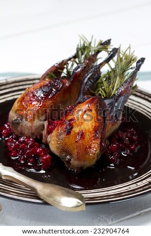 Roasted quails with rosemary and cranberry sauce - stock photo