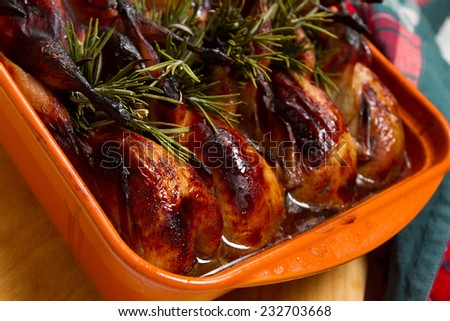 Roasted quails with rosemary in a ceramic baking form - stock photo
