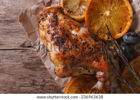 roasted rabbit leg with oranges, olives and rosemary on a paper on the old table. horizontal view from above, rustic style  - stock photo