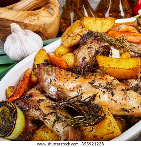 Roasted rabbit with herbs and vegetables - stock photo