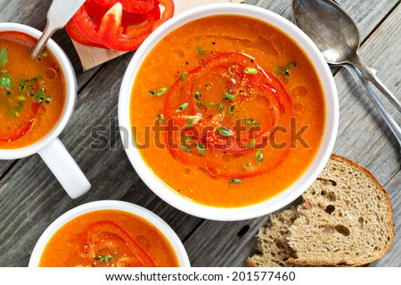 Roasted red pepper and carrot soup in white bowl - stock photo