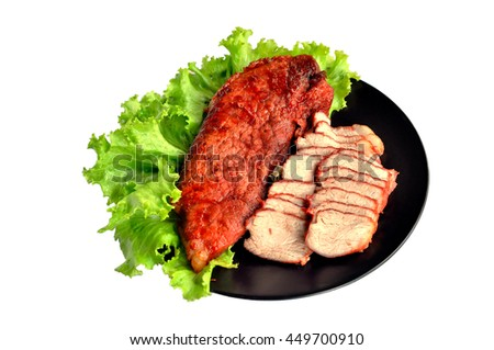 Roasted red pork on a green salad in a black plate. - stock photo