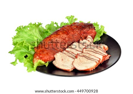 Roasted red pork on a green salad in a black plate.