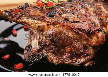 roasted ribs on black plate on wooden table